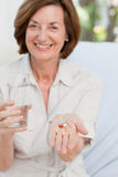 Cute mature woman with pills Royalty Free Stock Images