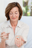 Cute mature woman with pills Stock Image