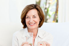 Cute mature woman with pills Royalty Free Stock Photos