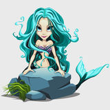Cute mermaid with long blue hair behind a rock. Cartoon character Stock Images