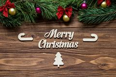 Cute Merry Christmas theme with cardboard candy canes and fir tree exposition on the wooden background Royalty Free Stock Photos