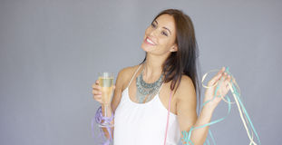Cute merry young woman partying at New Year. In en elegant evening outfit smiling with joy as she holds a glass of champagne and party streamers  on grey Stock Photo