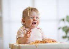 Cute messy baby crying while eating pasta at home. Cute messy baby girl crying while eating pasta at home stock image