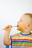 Cute Messy Infant Eating Side On Stock Photo