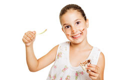 Cute messy little girl eating sweets Stock Photo