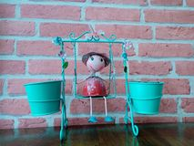 Cute metal girl doll is playing blue swing stock images