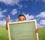Cute Mexican Boy Gives Thumbs Up in Field Holding Blank Chalk Board. Hispanic Boy with Thumbs Up in Grass Field Holding Blank Chalk Board Stock Photo