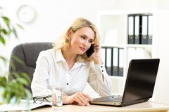 Cute middle-aged business woman working in office Stock Photo