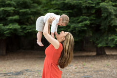Cute Millennial mother holding todddler son Royalty Free Stock Images