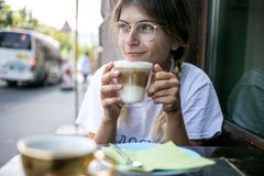 Cute pretty young woman drinks coffee milk foam royalty free stock image