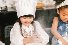 Cute mixed race and African American kid girls baking or cooking together in home kitchen. Education activity, youth culture, or smart young children concept royalty free stock photo