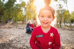 Cute Mixed Race Baby Girl Christmas Portrait With Family Behind. Outdoors royalty free stock photos