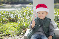 Cute Mixed Race Boy With Candy Cane wearing Santa Hat. Cute Mixed Race Boy Sitting Wearing Christmas Santa Hat and Enjoying A Candy Cane Stock Image
