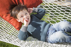 Cute Mixed Race Boy Relaxing in Hammock Stock Images