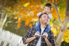 Cute Mixed Race Boy Riding on Shoulders of Caucasian Father Royalty Free Stock Photo
