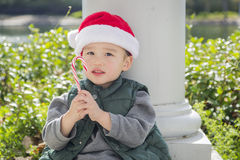 Cute Mixed Race Boy With Santa Hat and Candy Cane. Cute Mixed Race Boy Sitting Wearing Christmas Santa Hat and Enjoying A Candy Cane Stock Image