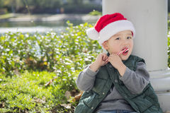 Cute Mixed Race Boy in Santa Hat eating Candy Cane. Cute Mixed Race Boy Sitting Wearing Christmas Santa Hat and Enjoying A Candy Cane Royalty Free Stock Photo