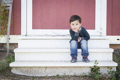 Cute Mixed Race Boy Sitting on the Steps of a Barn Stock Images