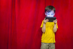 Cute Mixed Race Boy Watching Cell Phone by Red Curtain Royalty Free Stock Photos