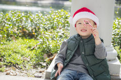 Cute Mixed Race Boy Wearing Santa Hat with Candy Cane. Cute Mixed Race Boy Sitting Wearing Christmas Santa Hat and Enjoying A Candy Cane Stock Photo