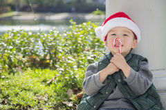 Cute Mixed Race Boy Wearing Santa Hat Eating Candy Cane. Cute Mixed Race Boy Sitting Wearing Christmas Santa Hat and Enjoying A Candy Cane Royalty Free Stock Photography