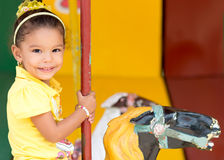 Cute mixed race girl riding a carousel Royalty Free Stock Image