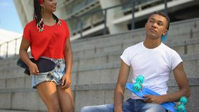 Cute mixed-race girl with skateboard sitting near guy, common interests, hobby. Stock footage stock video footage