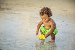 Cute mixed race little boy playing in the sand on a tropical beach vacation stock images