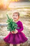 Happy Mixed Race Young Baby Girl Having Fun With Christmas Tree. Cute Mixed Race Young Baby Girl Having Fun With Christmas Tree Outdoors On Log royalty free stock photos