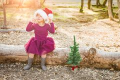 Cute Mixed Race Young Baby Girl Having Fun With Santa Hat and Christmas Tree. Outdoors On Log royalty free stock photography