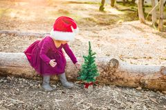 Cute Mixed Race Young Baby Girl Having Fun With Santa Hat and Tiny Tree. Cute Mixed Race Young Baby Girl Having Fun With Santa Hat and Christmas Tree Outdoors On royalty free stock photos