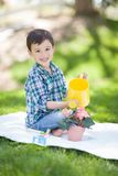Cute Mixed Race Young Boy Watering His Potted Flowers Outdoors On The. Mixed Race Young Boy Watering His Potted Flowers Outside On The Grass Royalty Free Stock Image