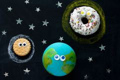 Model of the Earth, Sun and Moon with googly eyes on the chalkboard, a donut, a globe and a cookie on the chalkboard. Cute model of the Earth, Sun and Moon with stock image