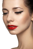 Cute model face with bright classical evening make-up, eyeliner on eyes, red lipstick Stock Photos