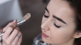 A cute model gets makeup put on before her shoot. Close up shot stock video footage