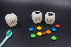 Cute modelo brinca os dentes e doces coloridos na odontologia em um fundo preto fotos de stock