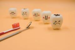 Cute modelo juega los dientes en odontología en un fondo amarillo Foto de archivo libre de regalías