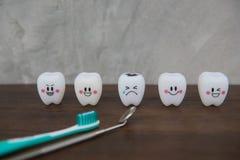 Cute modelo juega los dientes en odontología en un fondo de madera del gris de la tabla y de la pared Foto de archivo