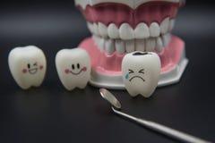 Cute modelo juega los dientes en odontología en un fondo negro Fotografía de archivo libre de regalías