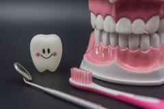 Cute modelo juega los dientes en odontología en un fondo negro Fotos de archivo