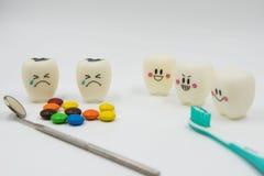 Cute modelo juega los dientes y el caramelo colorido en odontología en un fondo blanco Imágenes de archivo libres de regalías