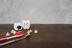 Cute modelo juega los dientes y el caramelo colorido en odontología en un fondo de madera del gris de la tabla y de la pared Fotografía de archivo libre de regalías