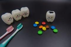 Cute modelo juega los dientes y el caramelo colorido en odontología en un fondo negro Imagen de archivo libre de regalías