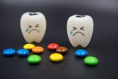 Cute modelo juega los dientes y el caramelo colorido en odontología en un fondo negro Fotografía de archivo