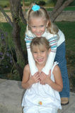 Cute Models. Give me a hug or lean on my. Two little girls smile for the camera and share a hug Stock Photo