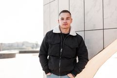 Cute modern young man with a stylish hairstyle in blue jeans in a trendy black jacket with a white collar resting standing. Near a wall in the city outdoors royalty free stock images
