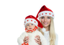 Cute mom and baby in santa hats Royalty Free Stock Photography