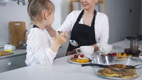 Cute mom and daughter cooking pancakes royalty free stock photography