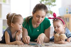 Cute mother and her two daughters children reading together royalty free stock photography