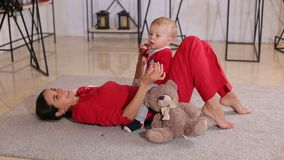 Cute mom playing with her little son lying on the floor of the house on a carpet. Cute young mom playing with her little son lying on the floor of the house on a stock video footage